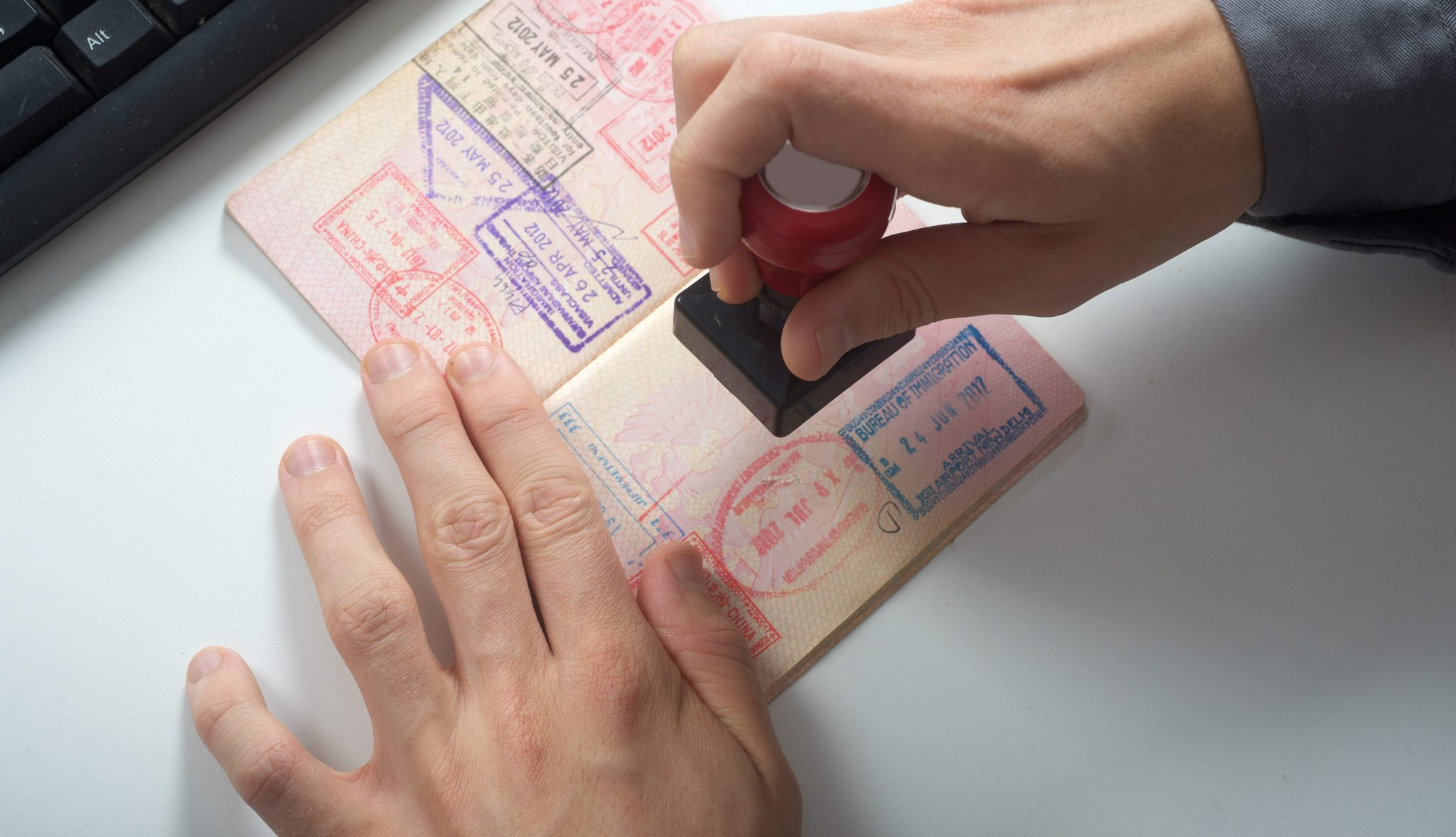 man stamps a passport for immigration