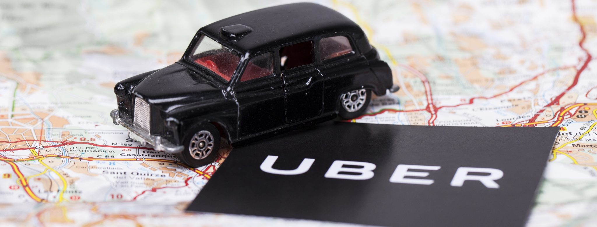 uber logo and toy car on map